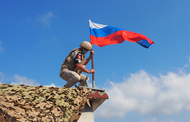 A Russian military police officer with a Russian national flag is seen during a joint patrol of the M4 Motorway with Turkish troops in the Idlib de-escalation zone in northeast Syria in Latakia Province, Syria on July 22, 2020. For the first time, Russia and Turkey jointly patrolled the whole M4 motorway to provide a safe link between Aleppo and Latakia. In March 2020, the presidents of Russia and Turkey met for talks in Moscow and reached an agreement about a ceasefire and joint patrols to alleviate the situation in north-eastern Syria. (Photo by Andrei Gryaznov/TASS via Getty Images)