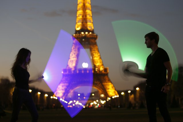 Marion (L) and Nikola (R), members of the Sport Saber League, pose with their light sabers in front of the Eiffel tower in Paris, France, November 26, 2015. (Photo by Charles Platiau/Reuters)