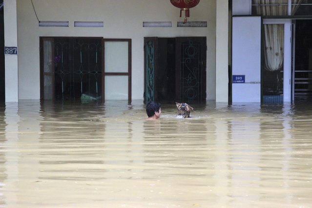 In this Sunday, June 24, 2018, photo, a man swims with his dog in the floodwaters in northern province of Ha Giang, Vietnam. Flash floods and landslides triggered by heavy rains hit northern Vietnam. (Photo by Minh Tam/Vietnam News Agency via AP Photo)