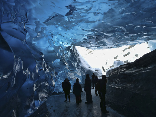 People check out the inside of an ice cave in Juneau, Alaska, on Sunday, February 7, 2021. The ice caves at the Mendenhall Glacier attracted a steady stream of visitors. The U.S. Forest Service has urged visitors to the glacier to be aware of the risks involved and to go prepared, saying a trip to or on the glacier is dangerous. (Photo by Becky Bohrer/AP Photo)