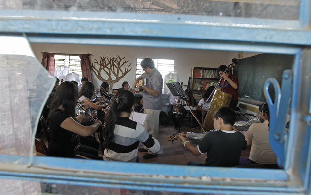 Director of the Orchestra of Recycled Instruments of Cateura, Favio Chavez (C, gray shirt), leads his music students during a rehearsal at the Vy'a Renda education center in Cateura, near Asuncion, May 8, 2013. The orchestra is the brainchild of its conductor Favio Chavez, who wanted to help the children of garbage pickers at the local landfill, and the instruments are made from salvaged materials by craftsman Nicolas Gomez. (Photo by Jorge Adorno/Reuters)