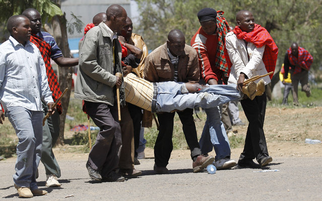 Residents carry a man shot and injured during protests to oust Narok county Governor Samuel Tunai in Narok, Kenya, January 26, 2015. (Photo by Thomas Mukoya/Reuters)