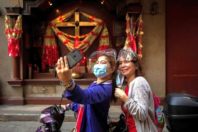 Women wearing masks and shields take a selfie in front of a praying altar during Lunar New Year in Chinatown in Manila, Philippines, February 12, 2021. (Photo by Eloisa Lopez/Reuters)