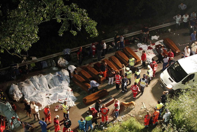 Bodies of victims are lined up after a coach crash near the southern town of Avellino July 29, 2013. At least 36 people died after the bus plunged more than 15 meters (49 feet) off a viaduct in southern Italy on Sunday, a spokesman for the fire service said. (Photo by Ciro De Luca/Reuters)