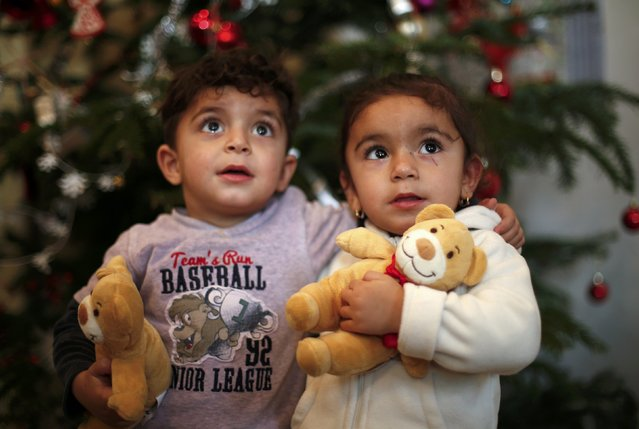 Two-year old twins Hevedar and Heve (R) of Iraq pose in front of a Christmas tree at a refugee shelter in an evangelic church in Oberhausen, Germany, December 22, 2015. (Photo by Ina Fassbender/Reuters)