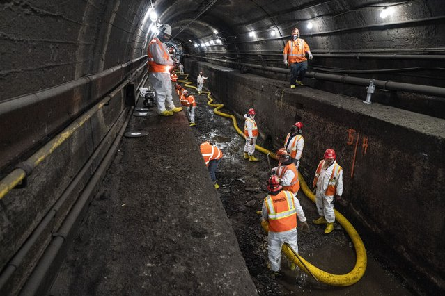 Amtrak workers perform tunnel repairs to a partially flooded train track bed, Saturday, March 20, 2021, in Weehawken, N.J. With a new rail tunnel into New York years away at best, Amtrak is embarking on an aggressive and expensive program to fix a 110-year-old tunnel in the interim. (Photo by John Minchillo/AP Photo)