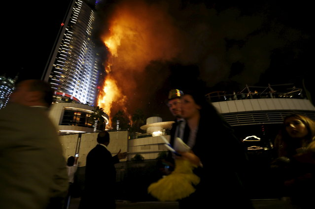 People run away as a fire engulfs The Address Hotel in downtown Dubai in the United Arab Emirates December 31, 2015. (Photo by Ahmed Jadallah/Reuters)