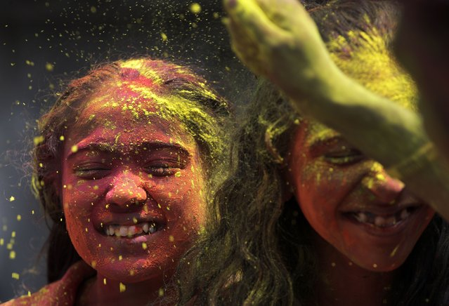 Indians throw colored powder on each other during Holi festival in Mumbai, India, Monday, March 29, 2021. (Photo by Rajanish Kakade/AP Photo)