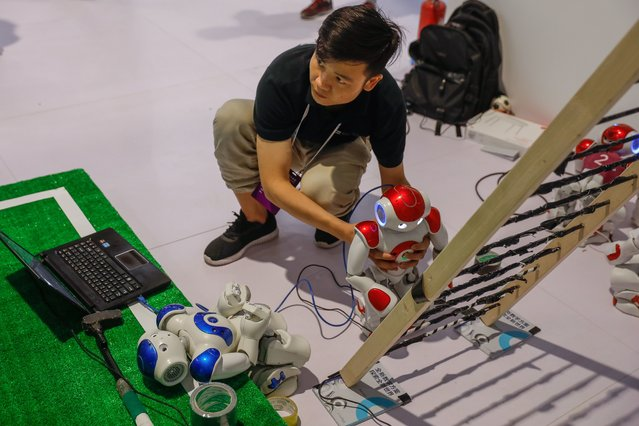 A Chinese participant adjusts robots during the 2018 World Robot conference in Beijing, China, 15 August 2018. (Photo by Roman Pilipey/EPA/EFE/Rex Features/Shutterstock)