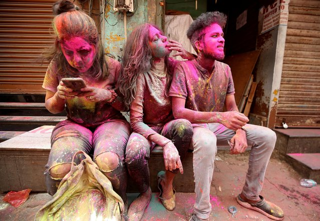 People daubed in colours rest as they take a break during Holi celebrations, amidst the spread of the coronavirus disease (COVID-19), in Chennai, India, March 29, 2021. (Photo by P. Ravikumar/Reuters)