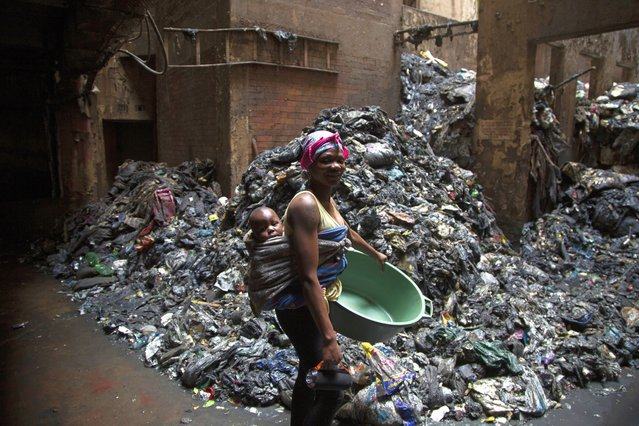 A woman with her child on her back goes about her daily chores as she passes piles of rubbish in a derelict building where she lives in Hillbrow, Johannesburg, South Africa, Monday, March 29, 2021. The building, which houses an orphanage, is being renovated to create accommodation in the inner city. (Photo by Denis Farrell/AP Photo)