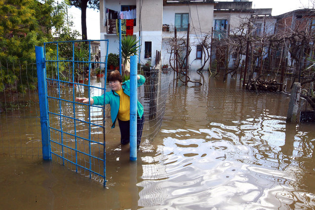 An Albanian woman tries to open the main gate outside her  flooded home in Darzeze village, Fieri district, 115 kilometers (75 miles) southwest of capital Tirana Saturday, February 7 2015. Flooding and cold weather have killed two women and left some 17,000 hectares (42,000 acres) under water. (Photo by Hektor Pustina/AP Photo)
