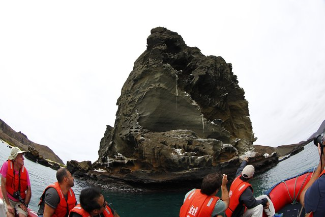 Tourists ride a boat as they look at the pinnacle rock at Bartolome Island in Galapagos August 23, 2013. (Photo by Jorge Silva/Reuters)