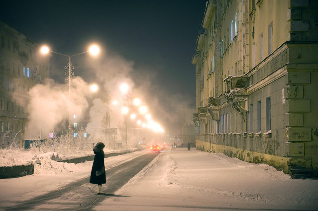 2012. A woman crosses the street on a freezing night. Norilsk is one of the coldest cities in the world: Winter temperatures average -22 F. It is covered in snow for eight to nine months of the year. It receives about 10 tons of snow per inhabitant and gets snowstorms about 130 days a year. (Photo by Elena Chernyshova)
