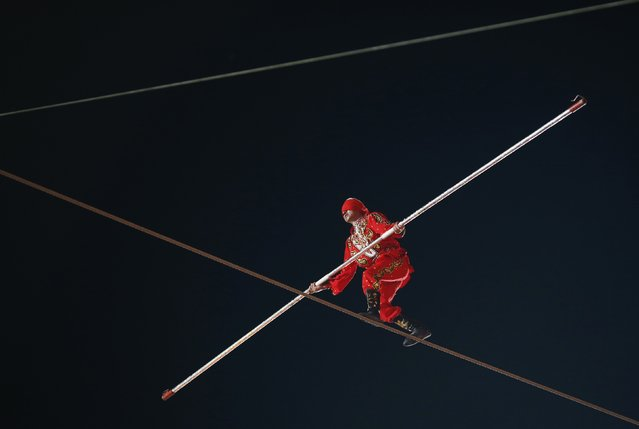 A member of the Acrobatic Troupe of Xinjiang, Abulaiti-Maijun, walks the tightrope blindfolded during an aerial performance at the River Hongbao Lunar New Year Celebrations along Marina Bay in Singapore February 17, 2015. (Photo by Edgar Su/Reuters)