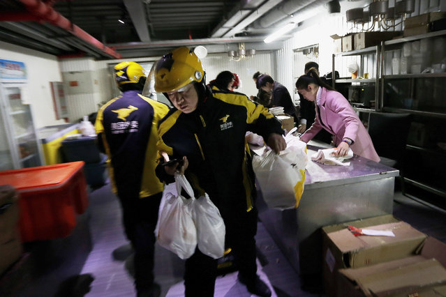 In this March 1, 2016, file photo, food delivery workers from Meituan, an E-commerce company, prepare to deliver orders placed online from a center in Beijing. Chinese food delivery giant Meituan said this week it raised nearly $10 billion in a sale of convertible bonds and additional shares and plans to invest those funds in developing and expanding delivery technologies. (Photo by Andy Wong/AP Photo/File)