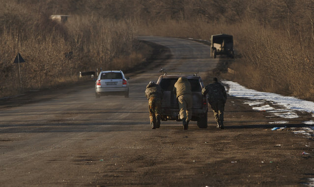 Ukrainian troops push a car as tehy attempt to start it, outside Artemivsk, Ukraine, while pulling out of Debaltseve, Wednesday, February 18, 2015. (Photo by Vadim Ghirda/AP Photo)