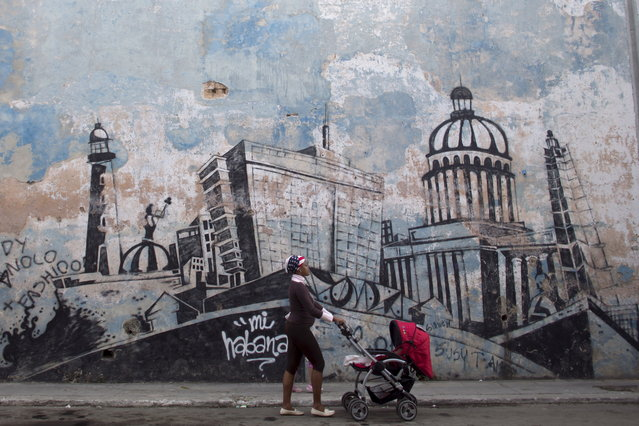 A woman pushes a stroller as she passes by a wall mural depicting Havana, in Havana, February 11, 2015. (Photo by Alexandre Meneghini/Reuters)