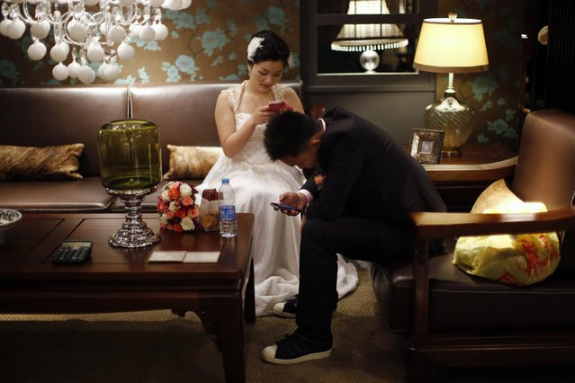 A couple is seen using their mobile phones as they wait to participate in a staged mass wedding, organised as part of a matchmaking event to inspire singles to get married, in Shanghai in this May 18, 2013 file photo. (Photo by Carlos Barria/Reuters)
