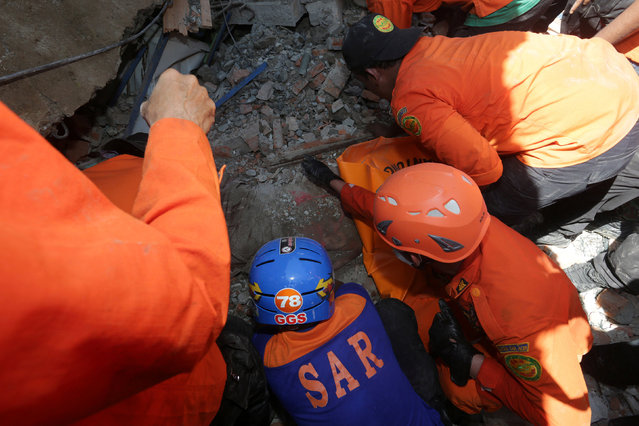 Rescue workers try to remove a victim from a collapsed building following an earthquake in Lueng Putu, Pidie Jaya in the northern province of Aceh, Indonesia December 7, 2016. (Photo by Irwansyah Putra/Reuters/Antara Foto)