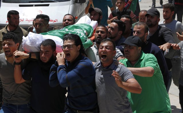 Mourners chant Islamic slogans while carrying the body of Awad Abu Selmiya, during a funeral of thirteen Hamas militants outside a mosque in Gaza City, Thursday, May 13, 2021. Gaza residents are bracing for more devastation as militants fire one barrage of rockets after another and Israel carries out waves of airstrikes. (Photo by Adel Hana/AP Photo)