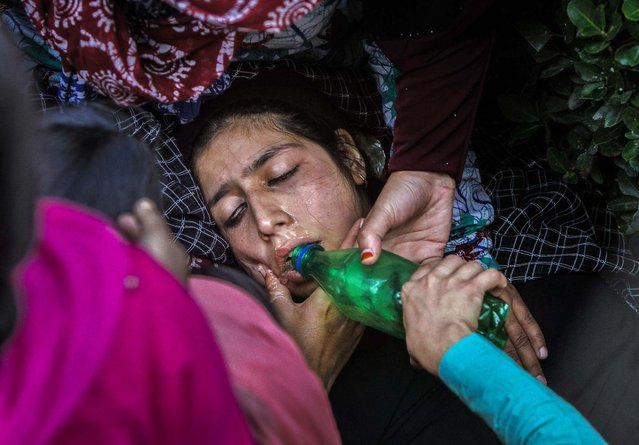Women comfort a teacher and offer her water after a fire broke out in a school building in Srinagar, India, on October 3, 2013. There were no immediate reports of injuries. (Photo by Mukhtar Khan/Associated Press)