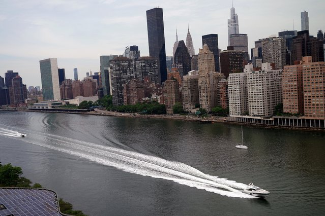 A boat passes by Manhattan as pictured from the Graduate Roosevelt Island hotel in New York City, New York, U.S., June 2, 2021. (Photo by Carlo Allegri/Reuters)