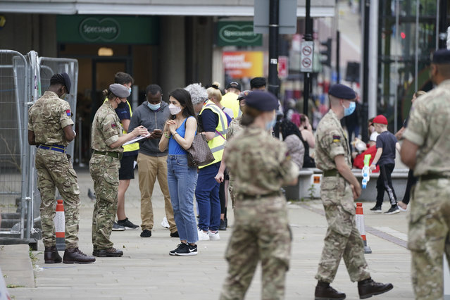 Members of the Armed Forces speak to people, outside a mobile COVID-19 vaccination centre outside Bolton Town Hall, in Bolton, England, Wednesday, June 9, 2021, where case numbers of the Delta variant first identified in India have been relatively high. (Photo by Peter Byrne/PA Wire via AP Photo)