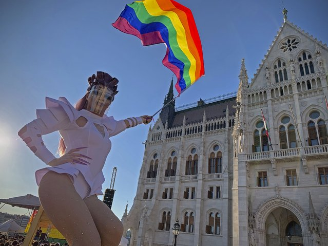 A drag queen waves a rainbow flag during an LGBT rights demonstration in front of the Hungarian Parliament building in Budapest, Hungary on June 14, 2021. During the protest human rights activists called on lawmakers in Hungary to reject legislation banning any content portraying or promoting homosexuality or sеx reassignment to anyone under 18. The bills, aiming at fighting pedophilia, have various amendments which would outlaw any depiction or discussion of different gender identities to youth in the public sphere. (Photo by Bela Szandelszky/AP Photo)