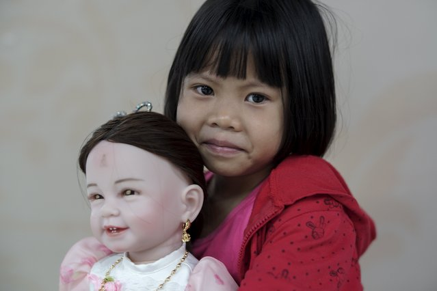 "Prew, 6, smiles as she holds up her ""child angel"" doll inside a department store in Bangkok, Thailand, January 26, 2016. (Photo by Athit Perawongmetha/Reuters)"
