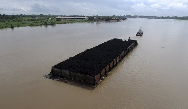 A barge carries coal on the Batang Hari River in Jambi province, Sumatra, Indonesia January 27, 2016 in this photo taken by Antara Foto. (Photo by Wahdi Septiawan/Reuters/Antara Foto)