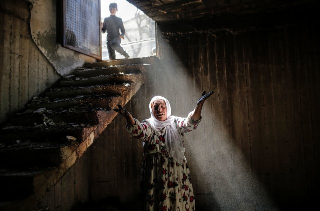 A woman reacts while walking among the ruins of damaged buildings following heavy fighting between government troops and Kurdish fighters, on March 2, 2016 in the southeastern Turkey Kurdish town of Cizre, near the border with Syria and Iraq. Thousands in Turkey's Kurdish-majority town of Cizre started returning to their homes today after authorities partially lifted a curfew in place since December for a controversial military operation to root out separatist rebels. (Photo by Yasin Akgul/AFP Photo)