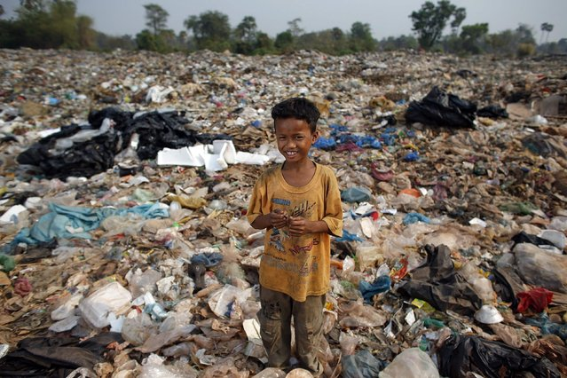 Ty, a 15-year-old boy, poses for a picture while collecting usable items at a landfill dumpsite outside Siem Reap March 19, 2015. Ty, who finished  six-grade primary school, said he makes 5 USD per month working at the dumpsite. (Photo by Athit Perawongmetha/Reuters)