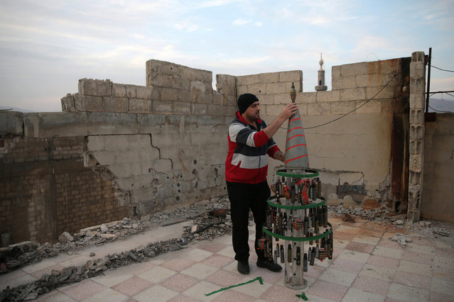 Akram Abu al-Foz, decorates a christmas tree from empty shells he collected and drew on, in the rebel held besieged city of Douma, in the eastern Damascus suburb of Ghouta, Syria December 23, 2016. (Photo by Bassam Khabieh/Reuters)