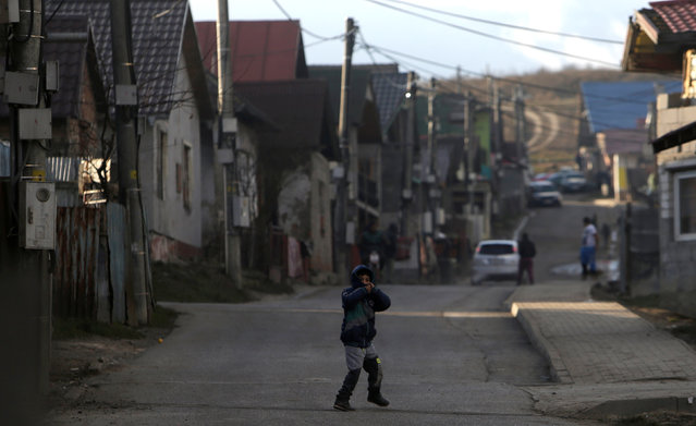"""SLOVAKIA: A Roma child walks across a street past refurbished houses near the so called """"Sheffield Square"""" in the town of Bystrany, Slovakia, November 28, 2016. (Photo by David W. Cerny/Reuters)"""