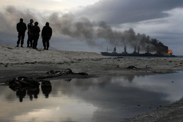Bystanders watch as the stranded bulk coal carrier Seli 1 burns off Cape Town's Blouberg beach, South Africa, June 3, 2010. (Photo by Mark Wessels/Reuters)