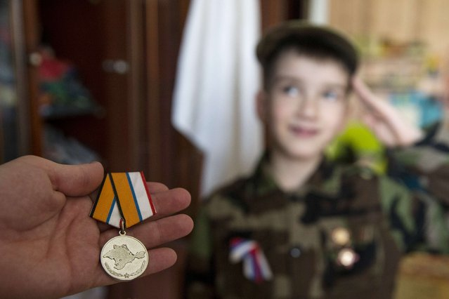 Valery, 30, a member of the People's Militia of Crimea, shows a medal, which was presented to him for merits while serving in a self-defence unit, with his son Kirill saluting in the background, inside their house on the first anniversary of the Crimean referendum to secede from Ukraine and join Russia, in Simferopol March 16, 2015. (Photo by Maxim Shemetov/Reuters)