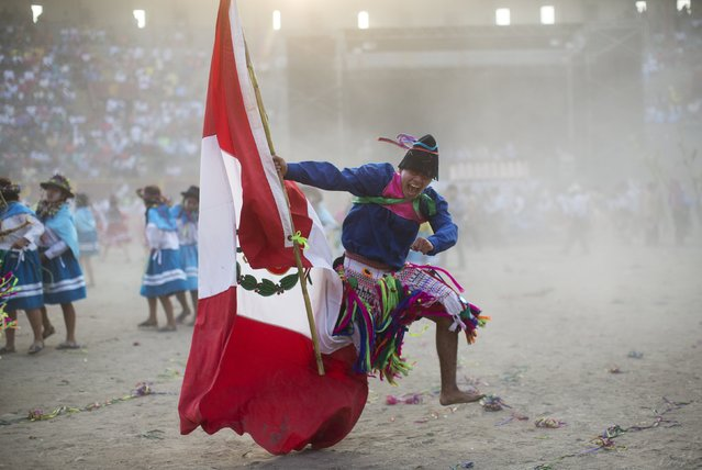 In this Sunday, March 29, 2015 photo, a man from the La Mar district of Ayacucho sings in Quechua, holding a Peruvian national flag as he performs in the Vencedores de Ayacucho dance festival, in the Acho bullring in Lima, Peru. The different dance troupes that perform during the one-day competition typically bring a representation of Peru's national flag to assert their nationality as well as their ethnic background. (Photo by Rodrigo Abd/AP Photo)