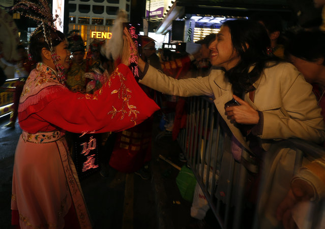 A spectator greets a Chinese dance performer during a Lunar New Year parade celebrating the first day of the Lunar New Year of the Monkey in Hong Kong, China February 8, 2016. (Photo by Bobby Yip/Reuters)