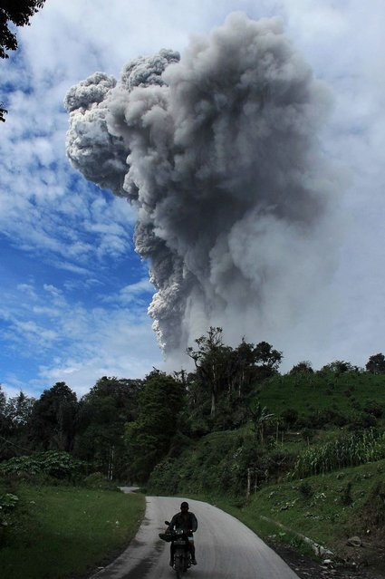 This picture taken on November 24, 2013 shows Sinabung volcano spewing volcanic ash in Karo. Several thousand people left their homes overnight, taking the total number of those who have fled since the volcano rumbled to life to around 12,300, said the national disaster agency. (Photo by Kharisma Tarigan/AFP Photo)