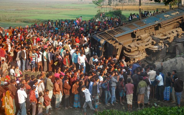 Bangladeshi onlookers gather at the scene of a derailed train in Gaibandha, some 200 kms north from Dhaka, on December 4, 2013. Opposition activists derailed a train in Bangladesh December 4, killing three people, as part of a campaign against elections due to be held next month, officials said. (Photo by AFP Photo/STR)