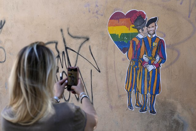 A murales showing a Swiss guard kissing a colleague, by street artist Laika, is seen on the day of the annual Pride march, in Rome, Saturday, June 26, 2021. This year's march comes amid widespread concern in Europe about legislation in Hungary that will ban showing content about LGBT issues to children and a controversial Vatican communication to Italy, criticizing a law that would extend additional protections from discrimination to the LGBT community. (Photo by Gregorio Borgia/AP Photo)