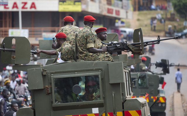 Ugandan soldiers riding in armored personnel carriers equipped with heavy-calibre weapons patrol past dejected opposition supporters, shortly after the election result was announced, in downtown Kampala, Uganda, Saturday, February 20, 2016. (Photo by Ben Curtis/AP Photo)