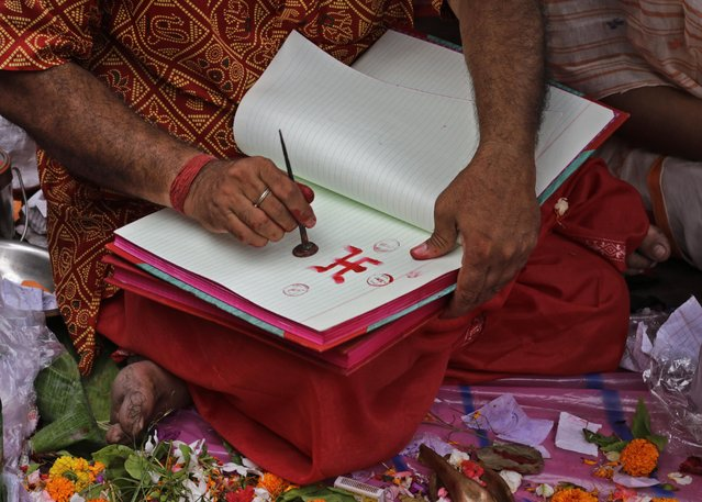 A Hindu priest marks a trader's account book with holy symbols on Bengali New Year day in Kolkata, India, Wednesday, April 15, 2015. Traders consider it auspicious to open their new account books on this day. (Photo by Bikas Das/AP Photo)