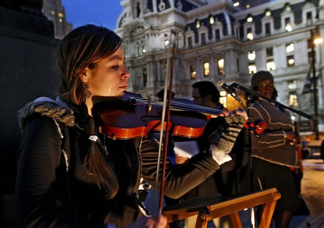 Tears stream down the face of Shandi Beardsley as she plays her violin while the names of the homeless who have died are read over the public address system to a crowd gathered at Thomas Paine Plaza in Philadelphia, for Homeless Memorial Day, on December 19, 2013. Nationally, remembrances are scheduled on or near the winter solstice, which is the longest night of the year. (Photo by Michael Bryant/The Philadelphia Inquirer)