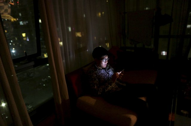 Online hostess fan Wang Dong watches a hostess singing, on a mobile phone, as he sits on a sofa at home in Beijing, March 20, 2015. (Photo by Jason Lee/Reuters)