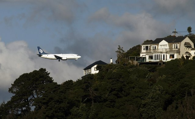An Air New Zealand plane flies over houses in Mount Victoria as it approaches Wellington airport, in this October 7, 2011 file photo. Air New Zealand is expected to report results this week. (Photo by Marcos Brindicci/Reuters)