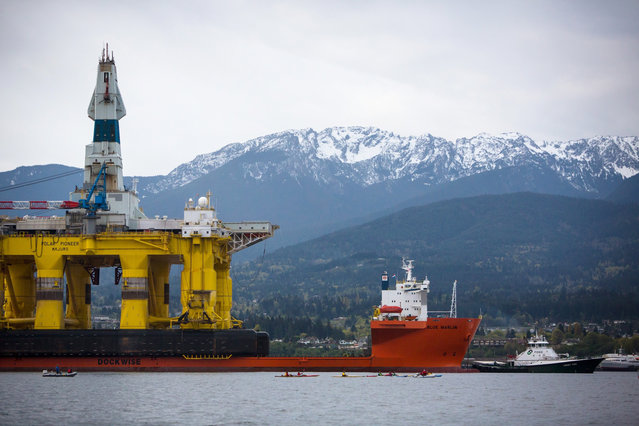 Protesters in kayaks are dwarfed as they paddle to meet an oil drilling rig as it arrives aboard a transport ship,  following a journey across the Pacific, Friday, April 17, 2015, in Port Angeles, Wash. (Photo by Daniella Beccaria/Seattlepi.com via AP Photo)