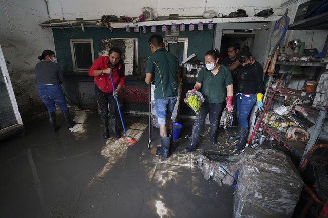 Locals start clean-up and recovery work after floods in downtown Tula, Hidalgo state, Mexico, Thursday, September 9, 2021. Teams continued evaluating the damage from flooding that swamped downtown Tula, when the Tula River jumped its banks. (Photo by Marco Ugarte/ AP Photo)