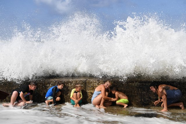 Locals shelter behind a sea wall as large waves generated by cyclone Oma crash onto it at Snapper Rocks on the Gold Coast, Queensland, Australia, 24 February 2019. Huge swells and high tides are pummeling south-east Queensland beaches as Cyclone Oma sits off the Queensland coast. According to the Australian Bureau of Meteorology, Cyclone Oma, now a subtropical cyclone, has changed direction away from Queensland, while strong winds and high waves will continue affecting the region. (Photo by Dan Peled/EPA/EFE)